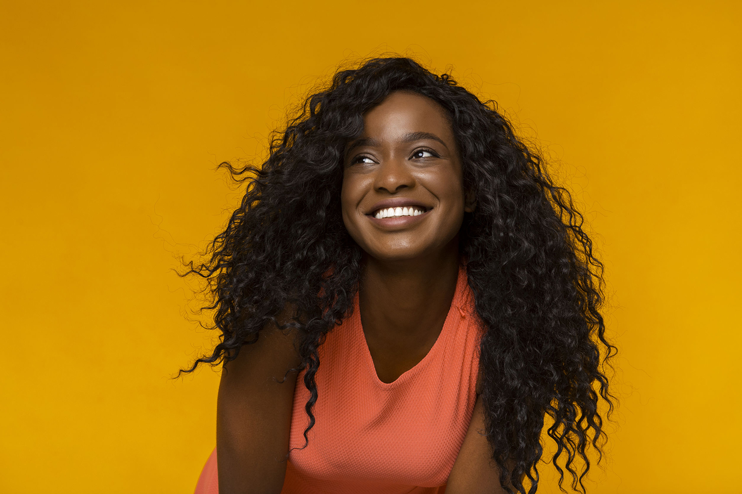 Excited african woman with wide smile looking aside